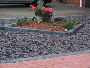 Slate front garden with centre-piece of flowerbed, edged by block paving. Calder Crescent, Taunton.