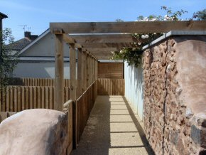 Pergola and close board fencing make an attractive walkway.