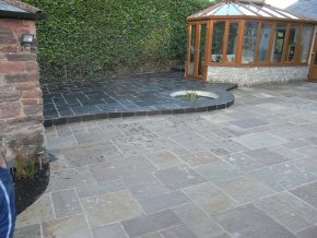 The garden is landscaped using a retaining wall around a patio area which has been paved leading to the garden.